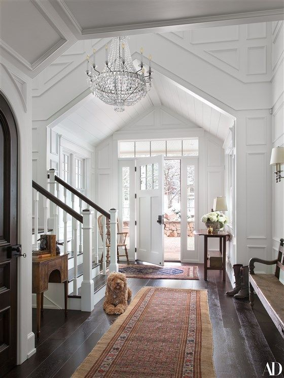 hallway, white wall, white ceiling, vaulted ceiling, wooden floor, rugs, wooden bench, wooden chair, wooden console table, crystal chandelier