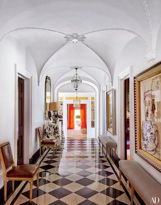 hallway, white wall, white dome ceiling, white black floor tiles, grey bench, leather chairs, crystal chandelier