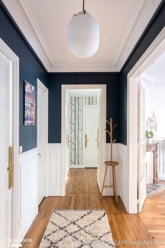 hallway, wooden floor, white wainscoting, dark blue wall, white ceiling, white door, white pendant