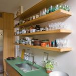 Kitchen, Brown Floor Tiles, White Wall, Wooden Bottom Cabinet, White Wall, Wooden Floating Shelves, Green Kitchen Top