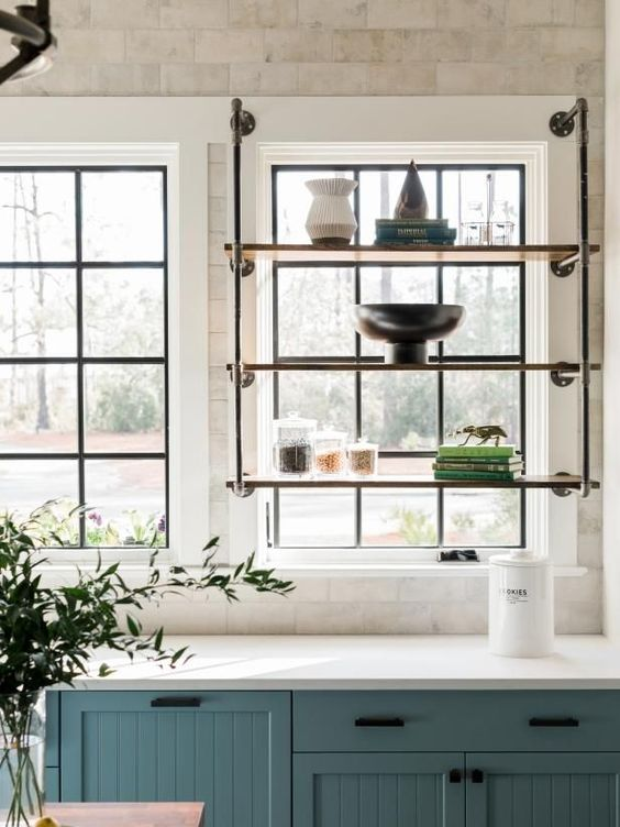 kitchen, white marble wall tiles, blue bottom cabinet with white top, metal shelves on the window