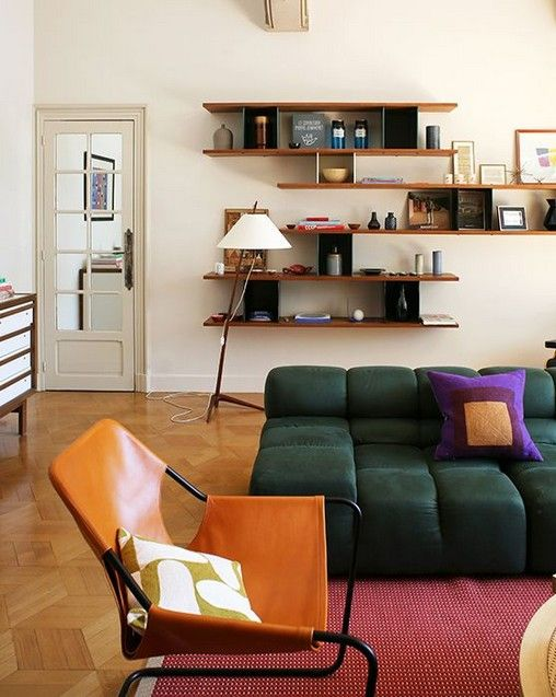 living rm, wooden floor, white wall, floating shelves, green sofa, red rug, orange chair, floor lamp