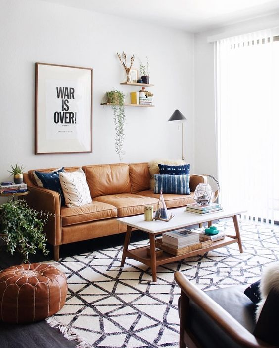 living room, dark wooden floor, white wall, brown leather sofa, black leather chair, white black rug, white coffee table