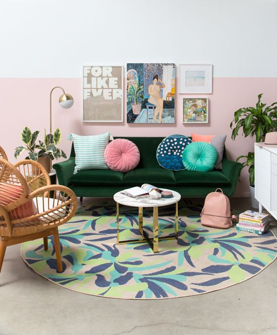 living room, grey floor, round colorful rug, white round coffee table, green velvet sofa, pink white wall, rattan chair, white cabinet