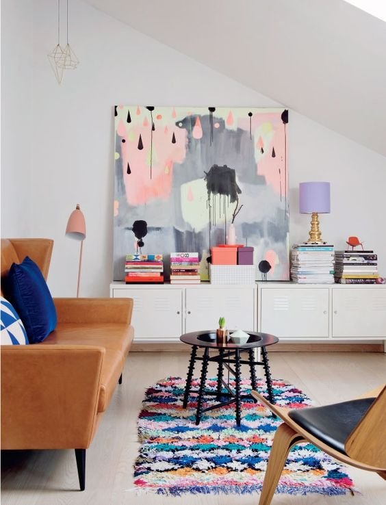 living room, light wooden floor, white wall, white cabinet, black round coffee table, brown leather sofa, pink floor lamp, wooden chair with black leather cushion