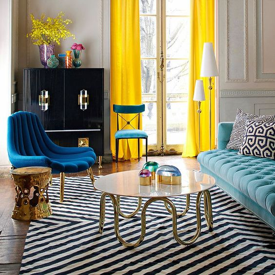 living room, white black lines rug, blue tufted sofa, dark blue chair, black cabinet, yellow curtain, white round coffee tble