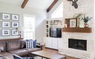 living room, wooden floor, white exposed wall, fireplace, brown leather sofa, simple wooden coffee table, white wall, white wooden ceiling with beams