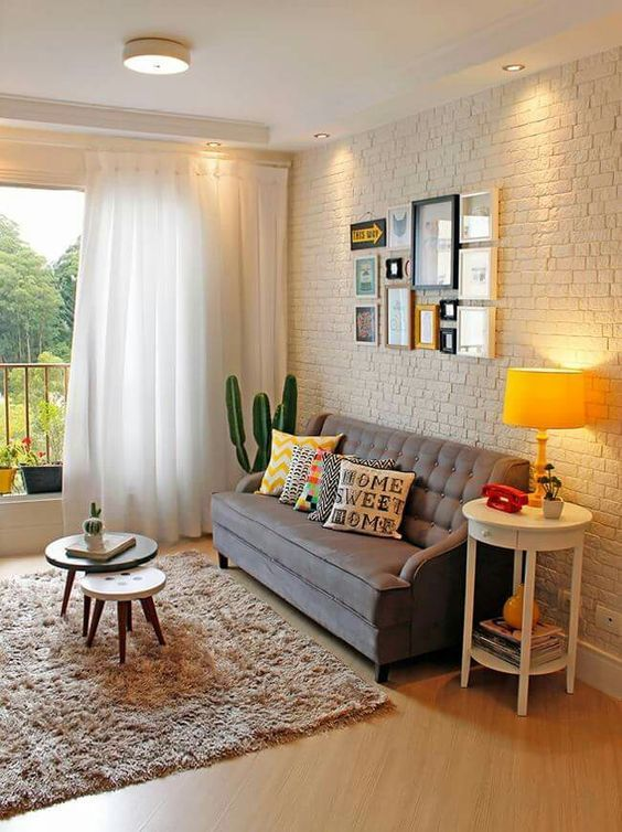 living room, wooden floor, white open wall, grey sofa, brown rug, white wide table, nesting table, yellow table lamp