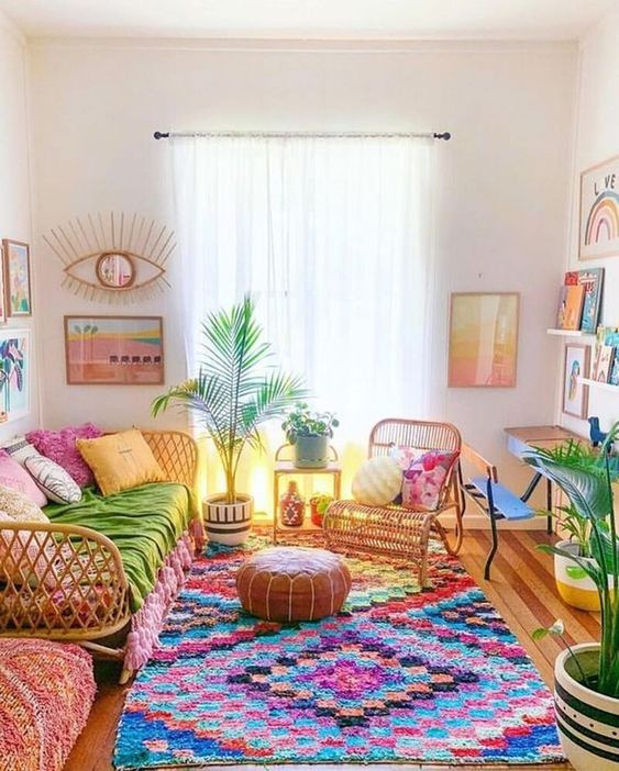 living room, wooden floor, white wall, floating shelves, rattan bench, rattan chair, brown leater ottoman, colorful rug, plant on pot
