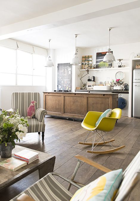 living room, wooden floor, white wall, stiped chairs, yellow rocking chair, kitchen island, white pendants