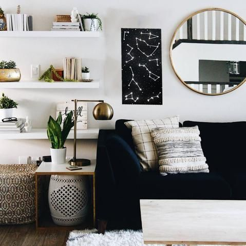 living room, wooden floor, white wall, white floating shelves, black sofa, wooden coffee table