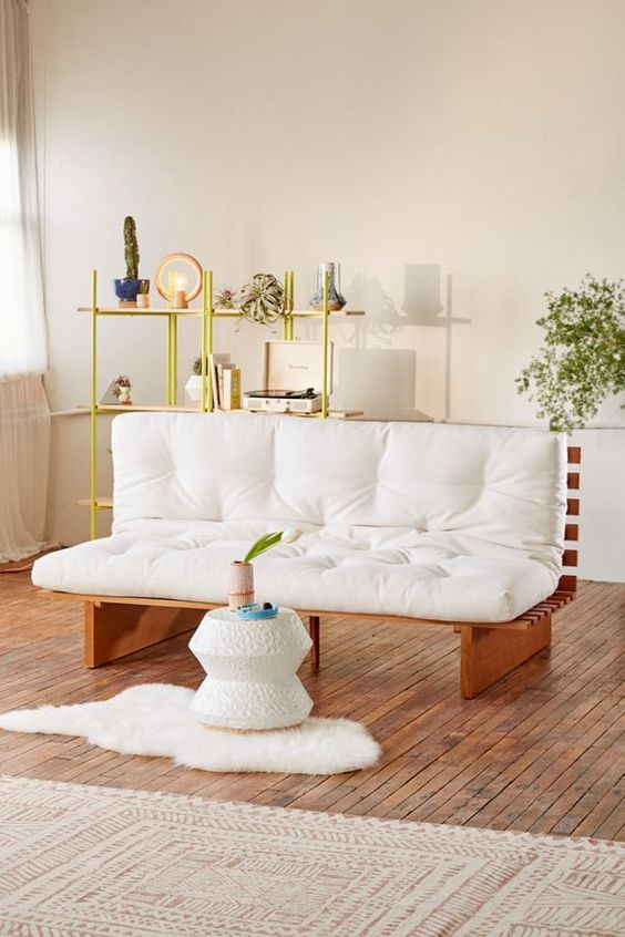 living room, wooden floor, wooden sofa with white cushion, white wall, white coffee table, green metal shelves
