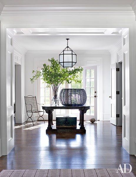 low foyer, white wall, white pendant, wooden table in the middle, wooden floor, plants on the table