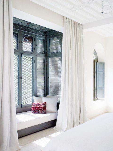 low window nook, white floor, white curtain, tall wooden window, white cushion, white pillows