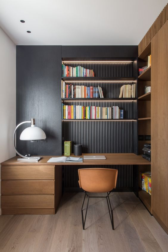 minimalist stud, wooden floor, black accent wall, built in shelves on the nook, wooden table with drawers, brown chair