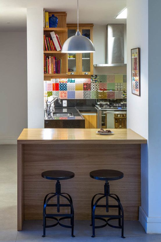 open kitchen, white wall, colorful backsplash tiles, wooden cabinet, silver top, wooden island, black stool, silver pendant