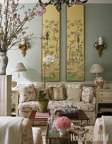 oriental painting , blue wall, flowery sofa, white wooden side table, flower