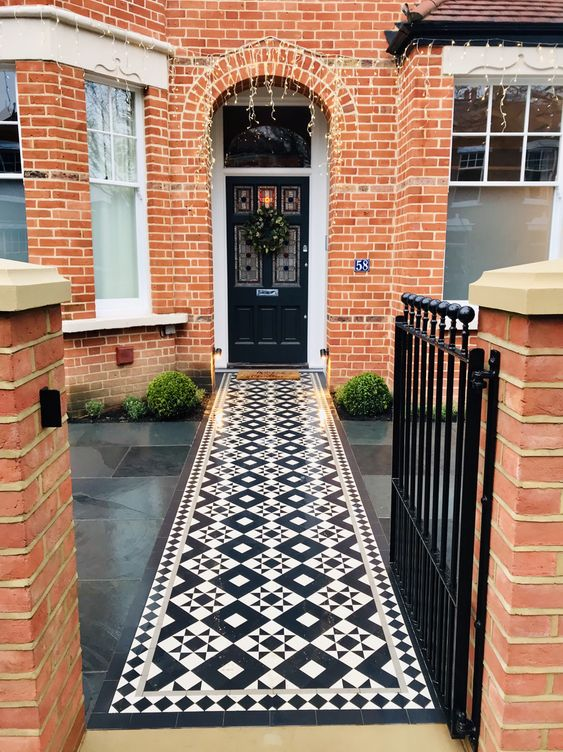 pathway, black tiles, black white patterned pathway, orange open wall, black fence