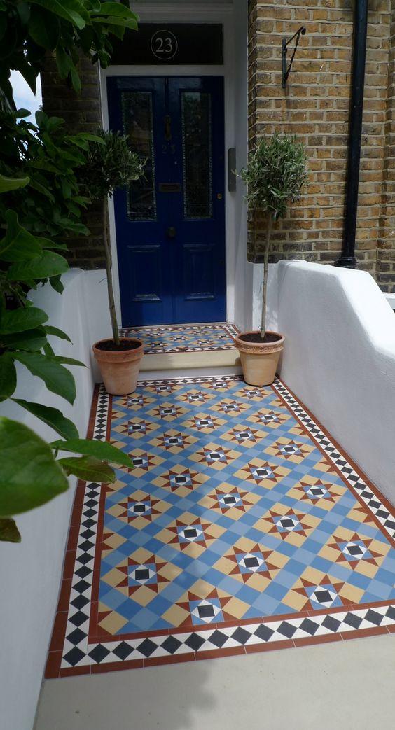 pathway, blue door, blue orange patterned floor tiles, white wall, open wall