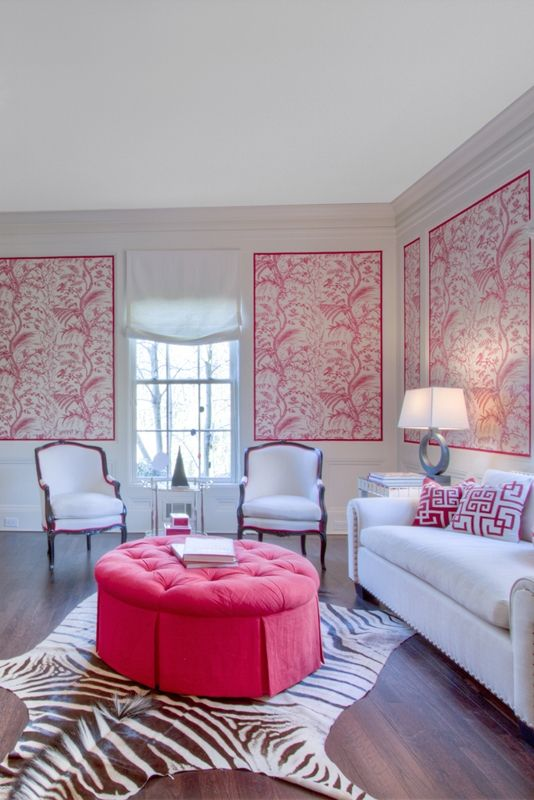 pink wall accent, white wall, wooden floor, white sofa, white chairs, white side table, pink tufted ottoman