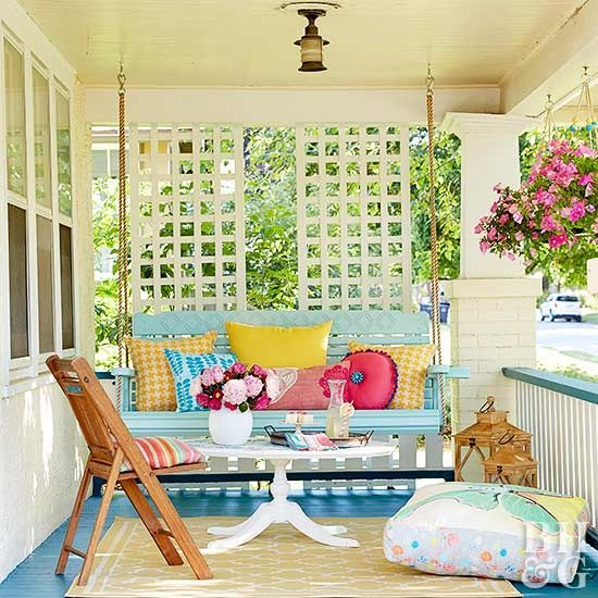 porch, blue wooden floor, white exposed brick wall, white wooden screen, blue wooden swing bench, white wooden round table, wooden chair, pillows