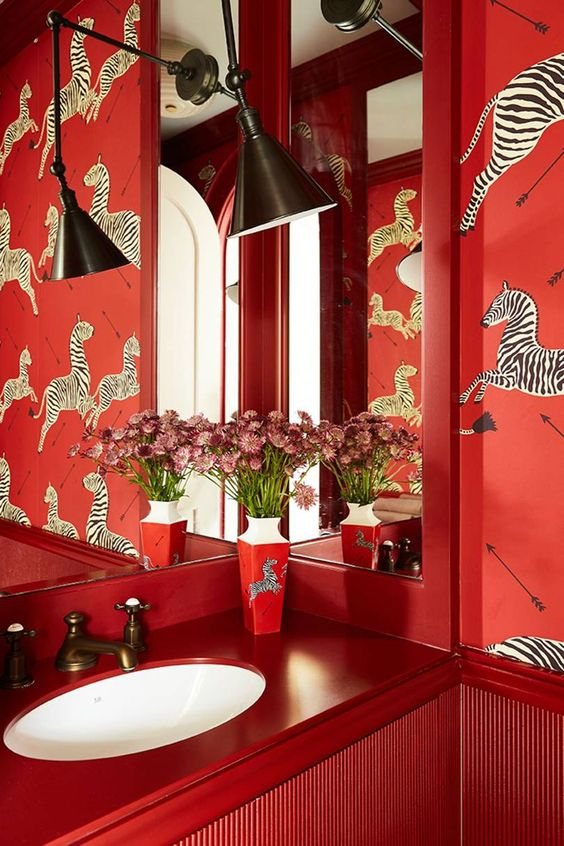 red vanity, red wallpaper with zebra prints, white sink