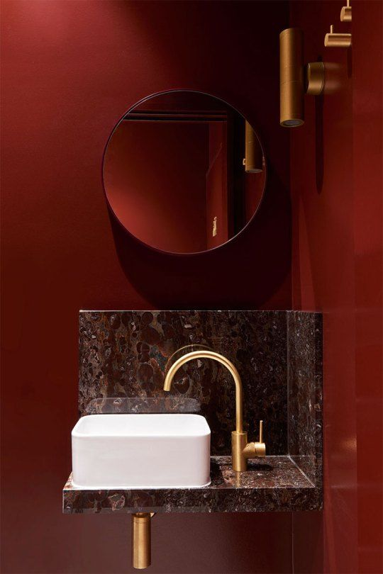 red wall, grey marble floating vanity, white sink, golden accent