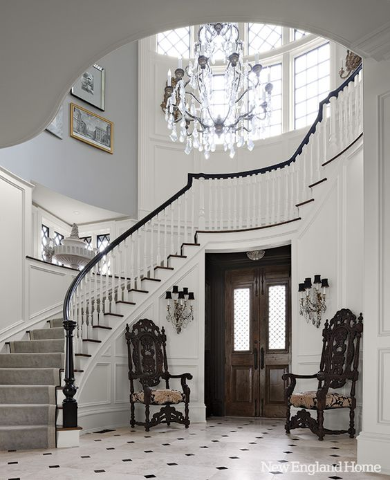 round foyer, tall ceiling, crystal chandelier, white wall, grey wall, white floor tiles, wooden chairs, dark wooden door, sconces