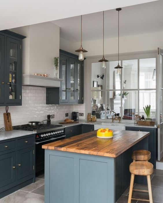 simple industrial pendant with long bulbs, wooden top blue island, wooden bar stools, white backsplash tiles, grey upper and bottom cabinet, white marble top