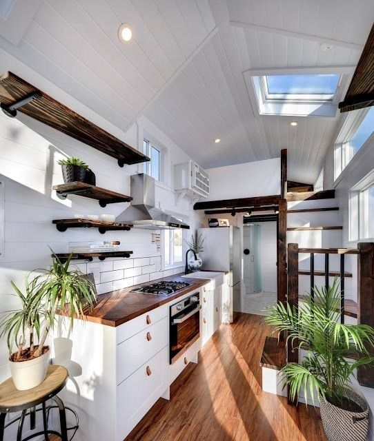 tiny house, wooden floor, white wall, white subway backsplash, floating shelves, white wooden stair, bedroom upstairs, bathroom at the end, glass ceiling