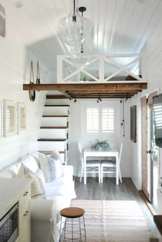 tiny house, wooden floor, white wooden wall and ceiling, dark wooden floor, white dinign set, white sofa, sliding door, bedroom upstair, melted glass pendant