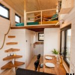 Tiny House, Wooden Floor, Wooden Wall, Kitchen At The Back, Dining Table, Black Sofa, Bed Upstairs, Corner Stairs Without Rail