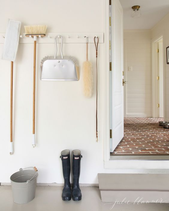 white wall, hooks, celaning tools hung,