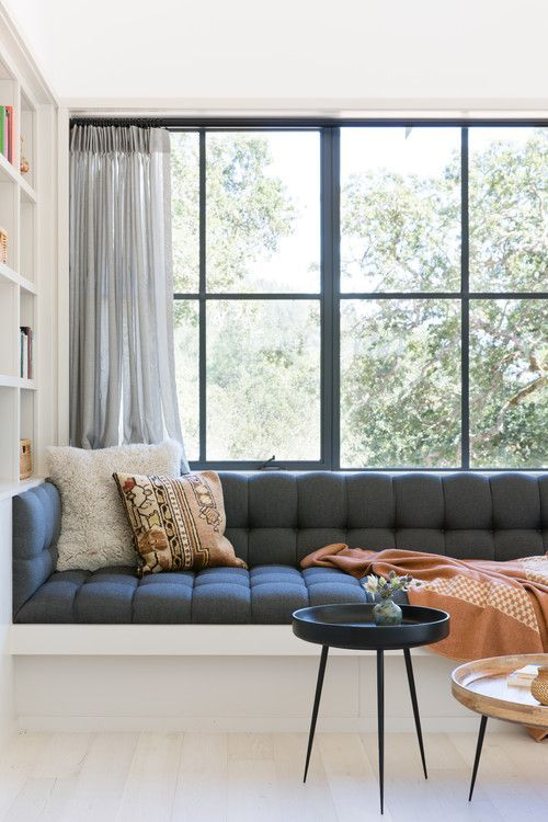 window seat, white built in bench, black tufted cushion, white built in shelves, glass window, tray coffee table