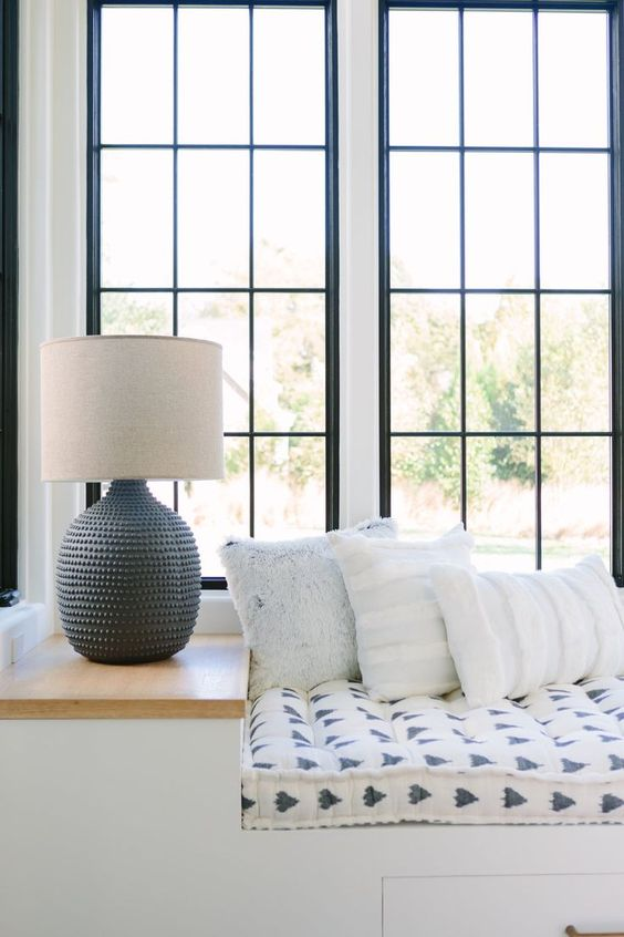 window seat, white built in bench, white patterned cushion, built in side table, tall glass window
