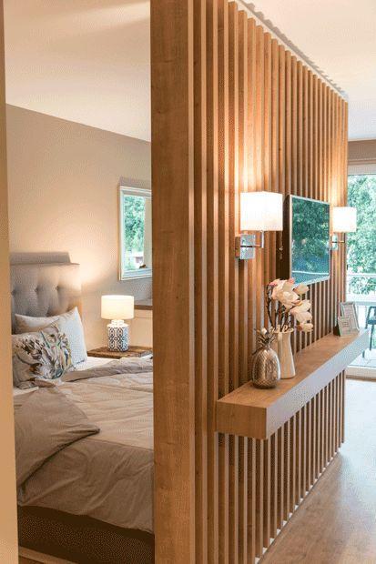 wooden grid partition on bedroom, floating shelves, sconces, lamp table
