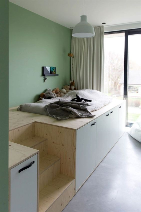 wooden platform, storage under, bed above on nook, stair, green wall, white pendant, large glass window