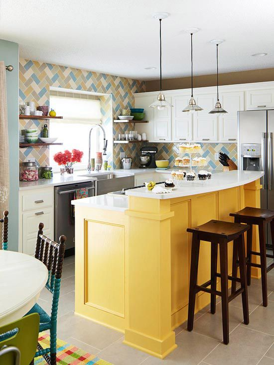 yellow island with white top, yellow blue wallpaper, white upper cabinet, grey floor, silver pendant