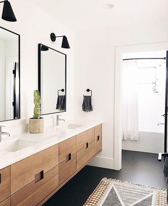 bathroom, black floor, white wall, floating wooden vanity, white top, black sconces, rug,