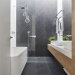 Bathroom, Black Herringbone Floor And Accent Wall, White Wall, White Tub, Floating Vanity, Glass Bulb Pendant, White Top, White Sink
