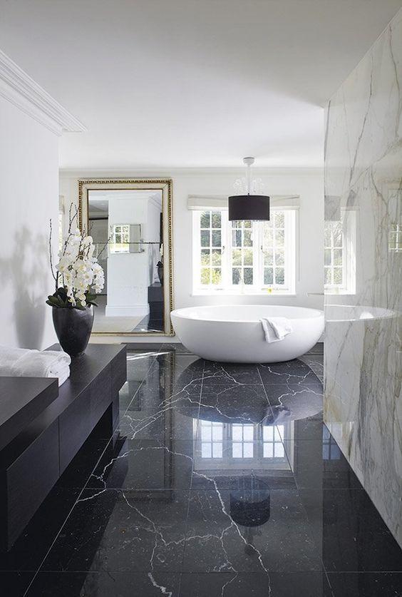 bathroom, black marble floor tiles, white marble wall, white round tub, black vanity
