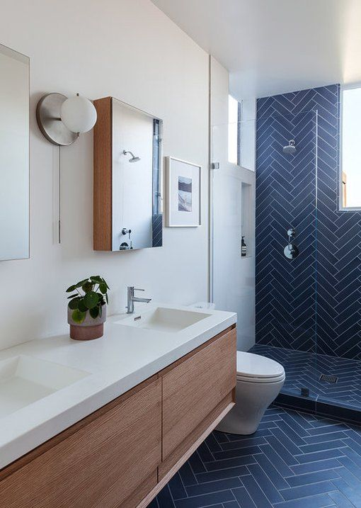 bathroom, dark blue herringbone tiles on wall and floor, white wall, wooden vanity cabinet with white top, white toilet