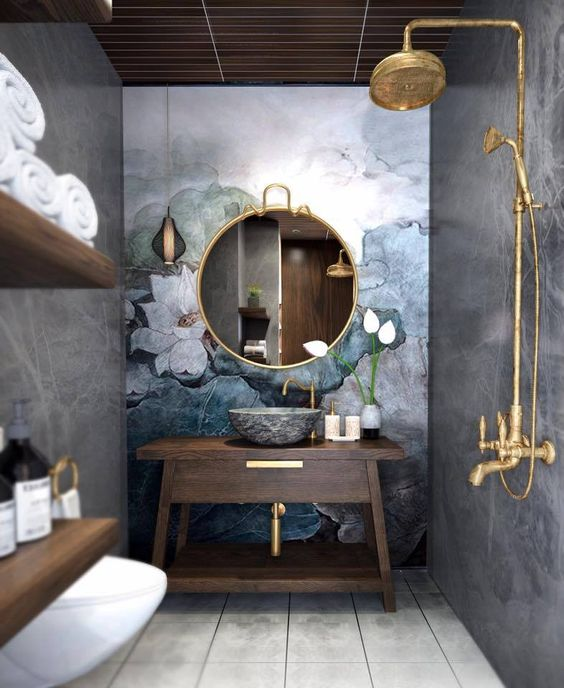 bathroom, grey wall, flower accent wall, golden round framed mirror, golden shower faucet, dark wooden vanity, wooden floating shelves
