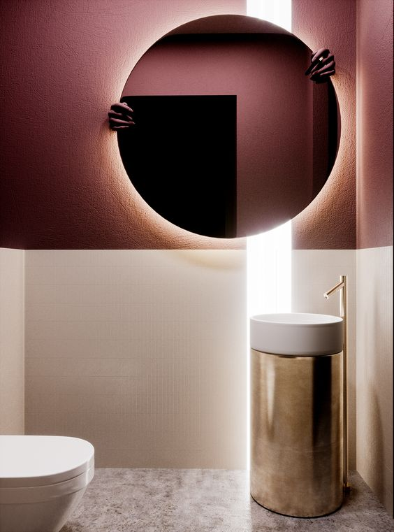 bathroom, marble floor, white pink wall, golden sink, white toilet, yellow LED lights behind round mirror
