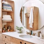 Bathroom Vanity, Wooden Door, White Counter Top, White Wooden Plank, Round Mirror, Wooden Shelves, White Bulb Sconces