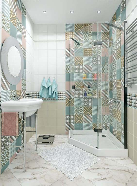 bathroom, white marble floor tiles, patterned accent wall tiles on the shower area and behind the mirror and white vanity, brown white wall tiles