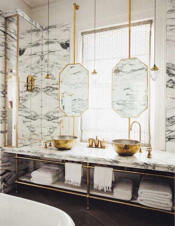 bathroom, white marble wall, golden framed mirror, golden sinks