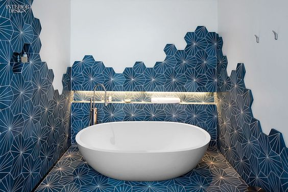 bathroom, white wall, blue geometrical tiles, indented wall for shelves, white bowl tub