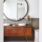 Bathroom, White Wall, Brown Subway Backsplash, Round Mirror, Wooden Cabinet, White Sinks, White Hexagonal Floor Tiles, Marble Tub