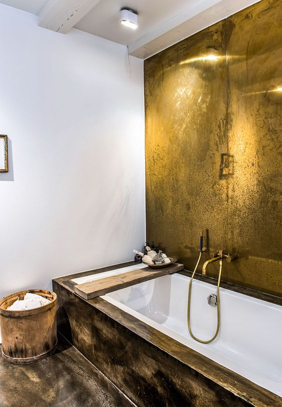 bathroom, white wall, golden accent wall, black and golden floor, golden faucet, white tub